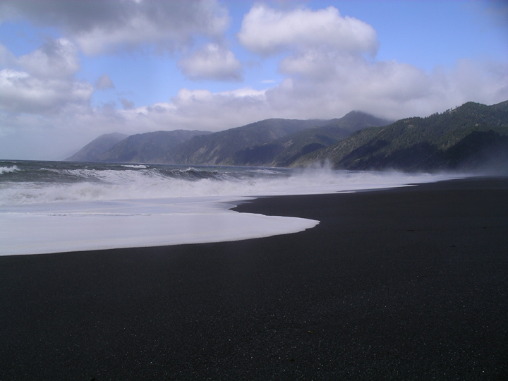 A beach appears blackened in the shadow of scattered clouds above with white waves crashing onto shore.